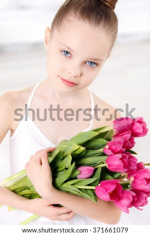 beautiful little ballerina with a bouquet of pink tulips, March 8, close-up - stock photo