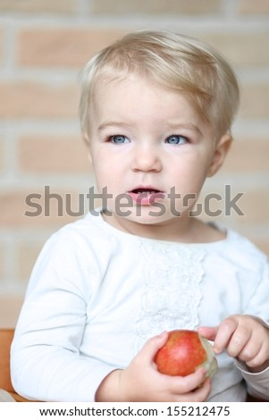 Beautiful little blond baby girl sitting in high feeding chair holding red apple in her hands - stock photo