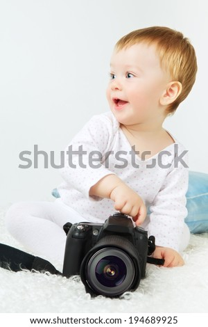 beautiful little blond baby with dslr camera - stock photo