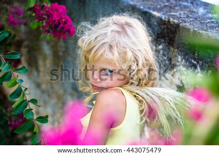 beautiful little blond girl and pink flowers - stock photo