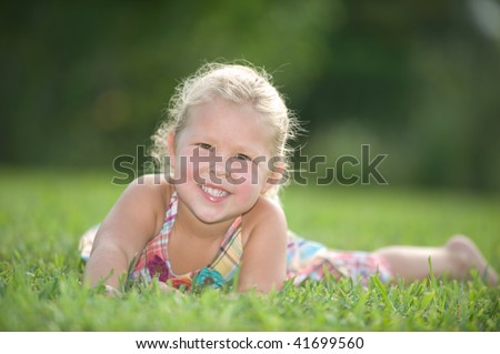 Beautiful little blond girl enjoying a day at the park - stock photo