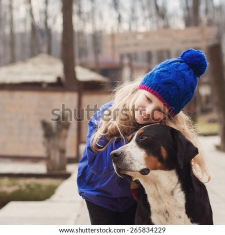 Beautiful little blond girl hugging a dog - stock photo