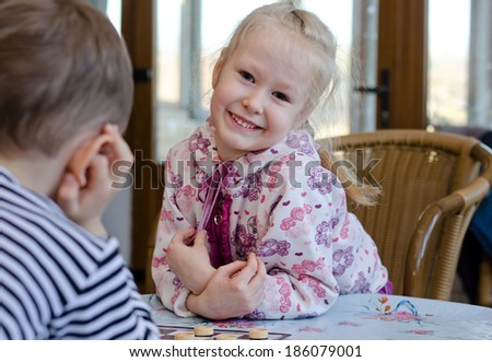 Beautiful little blond girl playing a game of checkers with her young brother sitting looking at the camera with a beaming happy smile - stock photo