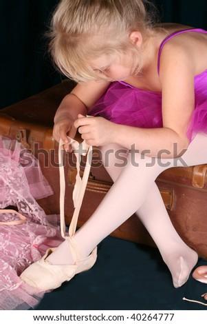 Beautiful little blond girl wearing a purple tutu - stock photo