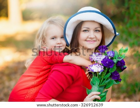 Beautiful little blonde girl and her mother, has happy fun cheerful smiling face, red dress, flowers eustoma. Family portrait nature.  - stock photo