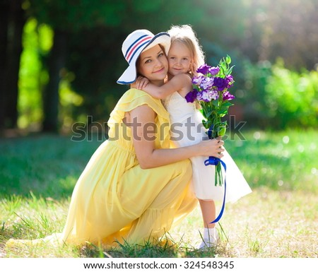 Beautiful little blonde girl and her mother, has happy fun cheerful smiling face, yellow and white dress, flowers. Family portrait nature.  - stock photo