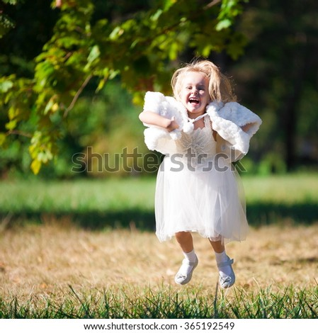 Beautiful little blonde girl, has happy fun cheerful smiling face, white dress. Portrait nature. Green garden. - stock photo