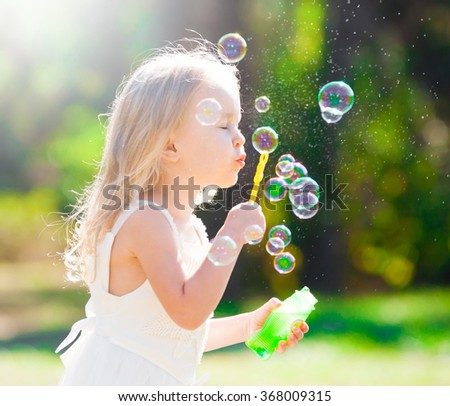 Beautiful little blonde girl, has happy fun cheerful smiling face, white dress, soap bubble blower. Portrait nature.