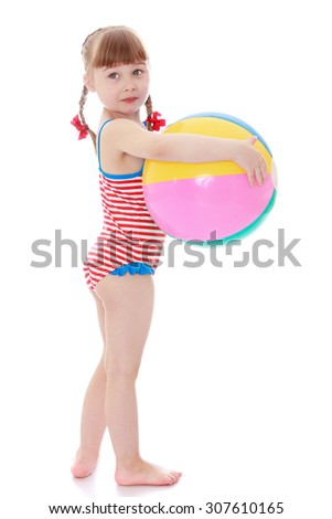 Beautiful little blonde girl with short bangs and long braids in which braided red bows holding the hand of a beach ball. The girl is dressed in a striped bathing suit . The girl turned sideways to - stock photo