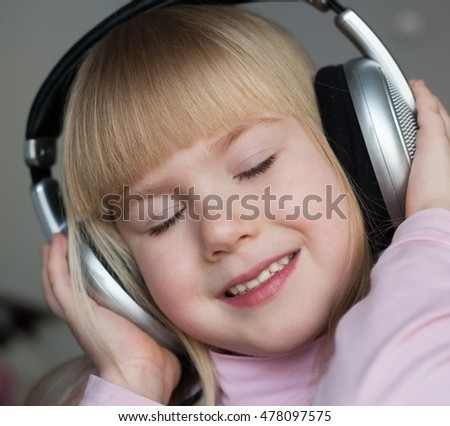 Beautiful little blonde hair girl, has happy fun smiling face, closed eyes. Pure skin. Child portrait. Listening and enjoying  to music on headphones.