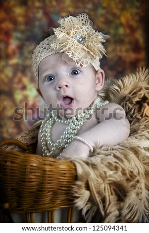 Beautiful little blue-eyed baby girl with bows,  pearls and fun expression - stock photo