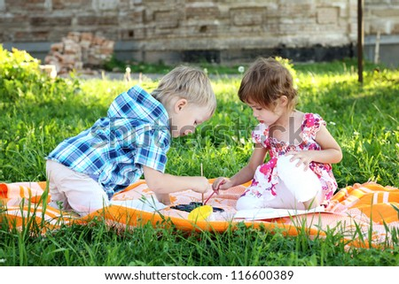 beautiful little boy and girl draw in summer park