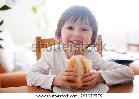 Beautiful little boy, eating sandwich at home, vegetables on the table, back light