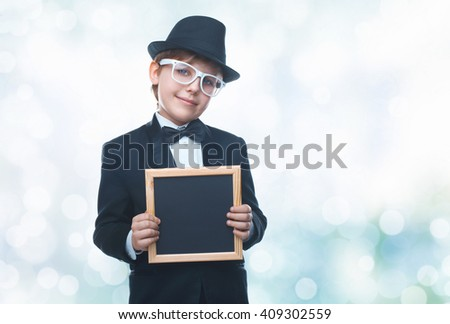 Beautiful little boy holding a board for chalk. Empty space for text. School lessons. Back to school. Colored backgrounds - stock photo