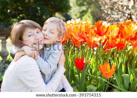 beautiful little boy hugging and kissing his young mother in the garden by blooming flowers celebrating mother's day together - stock photo