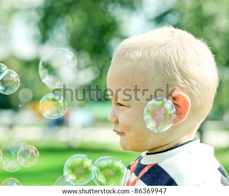Beautiful little boy inflating soap bubbles - stock photo