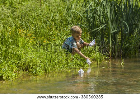 Beautiful little boy playing with paper boats by a river on warm and sunny summer day. Active leisure for children. Kid having fun outdoors. - stock photo