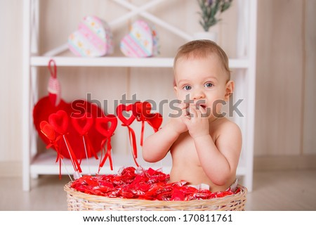 beautiful little boy sits among candies. valentine's day concept