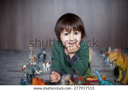 Beautiful little boy, smiling at camera, animals and dinosaurs around him, indoor shot - stock photo