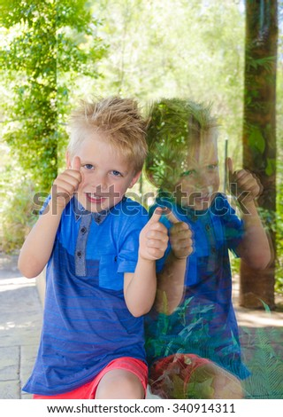 Beautiful little boy smiling next to a window - stock photo