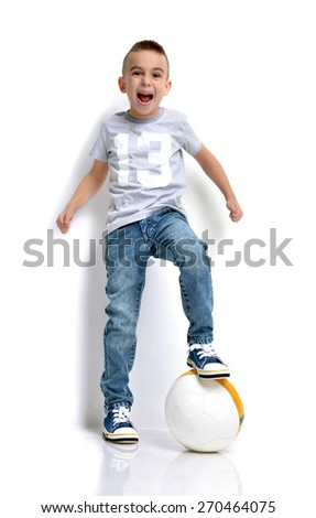 Beautiful little boy soccer fun player with ball yelling standing over white background - stock photo