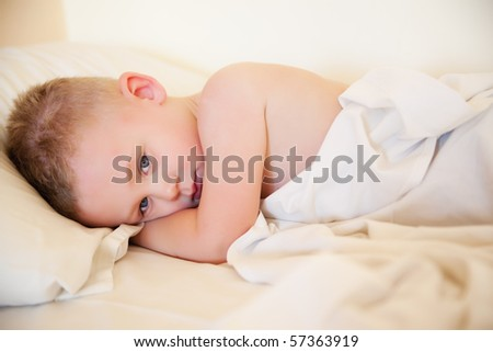 Beautiful little boy waking up in the morning - stock photo