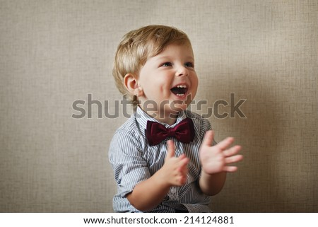 Beautiful little boy wearing a stylish maroon bow tie laughing and clapping his hands against a grey wall with vignetting - stock photo
