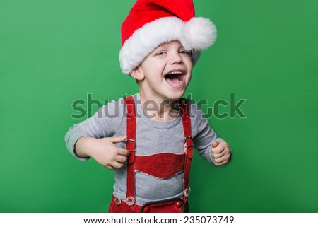 Beautiful little boy with Santa Claus hat laugh. Christmas concept. Studio portrait over green background  - stock photo
