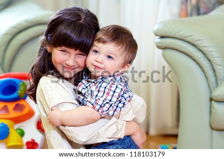 beautiful little brother and sister embracing in home interior - stock photo