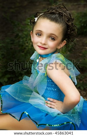 beautiful little brown-eyed, brunette girl with  make-up wearing a costume - stock photo