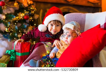 Beautiful little brunet boys, has happy fun smiling face, brown eyes, red Christmas hat Santa Claus. Close up. Winter holiday background. Family portrait. Blood brothers. Night light