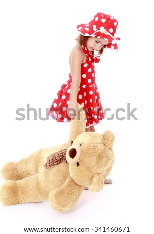 beautiful little Caucasian girl in a short red summer dress, and hat with polka dots pulls the paw of a big Teddy bear - Isolated on white background - stock photo