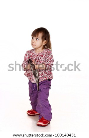 Beautiful little Caucasian girl posing with a fork on a white background