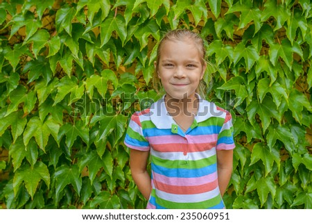 Beautiful little cheerful girl on background of fallen wall of wild grapes. - stock photo