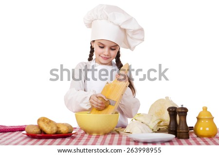 Beautiful little chief cooker on the desk with vegetables, isolated on white background - stock photo