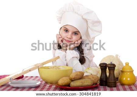 Beautiful little chief cooker on the desk with vegetables, isolated on white background