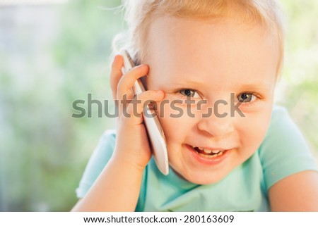 Beautiful little child talking by mobile phone with her mother. Girl is blonde with very beautiful eyes on a green background and she is happy - stock photo