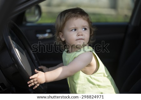 Beautiful little curious male kid driver sitting in big car with black salon holding wheel looking away through window in summer, horizontal picture - stock photo