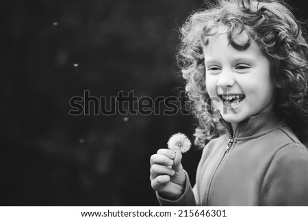 Beautiful little curly girl blowing dandelion, black and white portrait. - stock photo