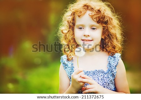 Beautiful little curly girl blowing dandelion, toning photo. Instagram filter. - stock photo