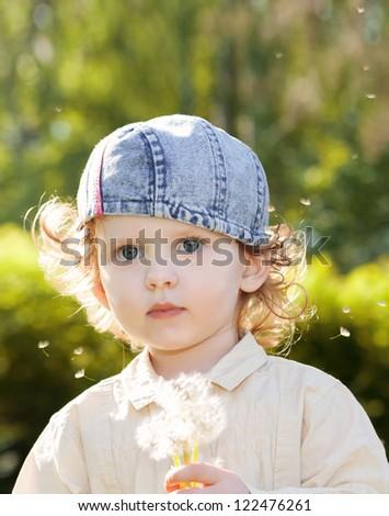 Beautiful little curly girl blowing dandelion,vertical shot - stock photo