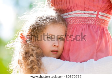 beautiful little daughter hugging her mother and looking into the camera. Nature background.