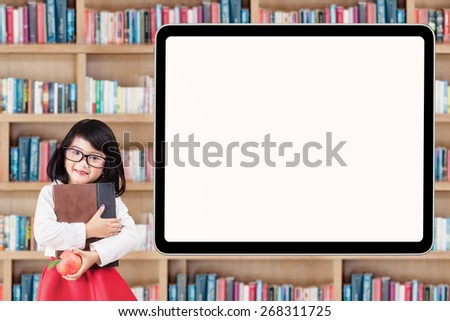 Beautiful little elementary school student smiling at the camera near the empty board in library - stock photo