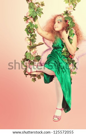 Beautiful little fairy swinging on a swing over pink background. - stock photo
