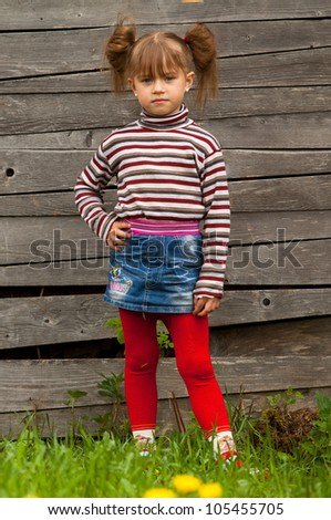 Beautiful little five-year girl posing for the camera outdoor near wooden wall - stock photo