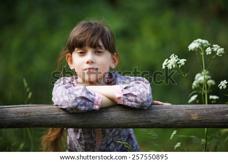 Beautiful little girl among the wildflowers in summer - stock photo