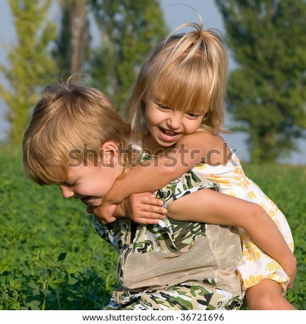 Beautiful  little girl and boy in the field - stock photo