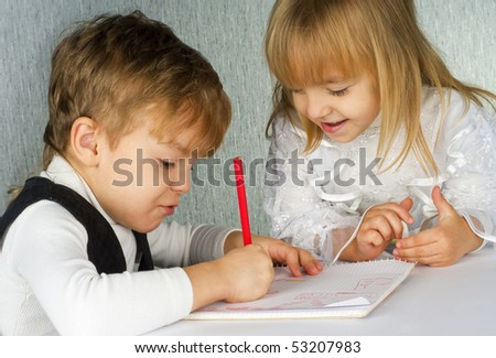 Beautiful little girl and boy is drawing with pencils on paper