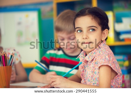 Beautiful little girl and her classmate at school - stock photo