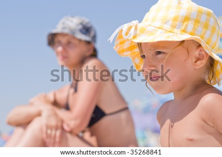Beautiful little girl and her mother with sun hat on beach - stock photo